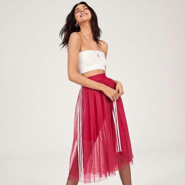 La jupe mi-longue rose Adidas avec rayures blanches sur les côtés de Kendall Jenner pour le lancement de la collection en Mai 2019