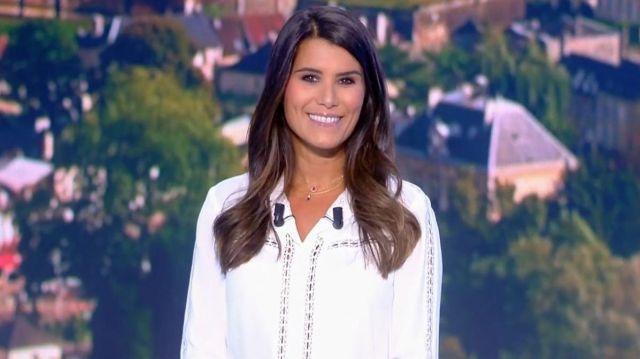 La chemise blanche col rond, apports dentelle devant, dos et sur les manche de Karine Ferri dans Tirage du loto le 26.09.2020